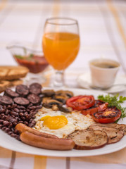 Full English fried breakfast with bacon, egg, sausages, black pudding, mushrooms, grilled tomatoes and baked beans. Closeup with toasts, cup of coffee, orange juice and home made  red sauce.