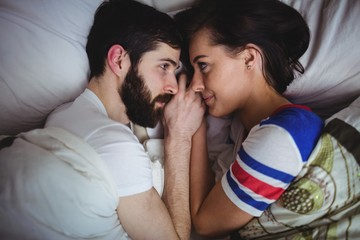 Couple looking at each other while lying on bed