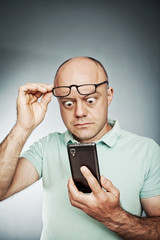 Image of an expressive middle aged man looking at his cell phone
