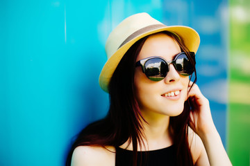 Smiling summer woman with hat and sunglasses over bright background.