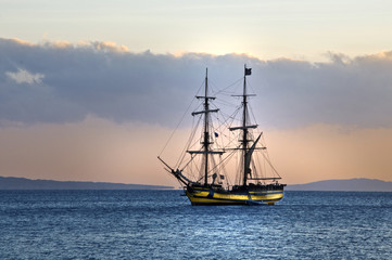 sailing ship at anchor, a blue calm sea and cloudless sky