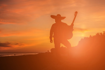 Mexican, Latin American, Spanish. Musician on the coast. Silhouette at sunset.