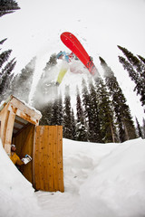 A male backcountry snowboarder airs an outhouse, Icefall Lodge, Canadian Rockies, Golden, BC