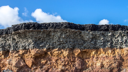 The curb erosion from storms. To indicate the layers of soil and