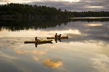 Young couple kayaking on Gull Lake near Gravenhurst, Ontario, Canada.