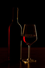 Red wine bottle with glass on black background - silhouette