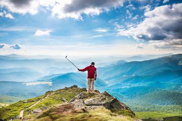 Young man on mountain taking selfie