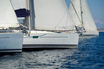 Sailing boats is crossing the regatta start line. Mediterranean sea charter racing.