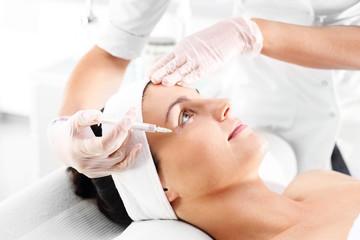 Zastrzyk z botoxu. Kosmetyczka ostrzykuje twarz kobiety