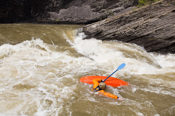 A male whitewater kayaker swims after getting caught in a rapid on the Highwood River, Alberta, Canada