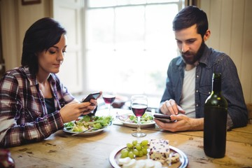 Couple using mobile phone while having breakfast