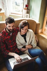 Couple using laptop in living room