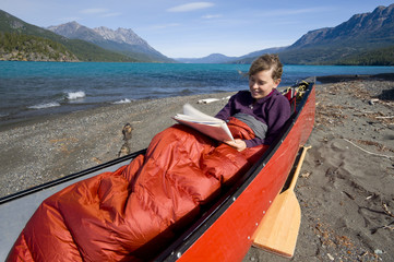 A young, attractive woman does a crossword puzzle sitting in a canoe on the shores of the azure Tatlayoko Lake, British Columbia, Canada