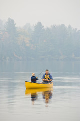 Young/middle-aged man fishing with son from canoe on Source Lake, Algonquin Provincial Park, Ontario, Canada.