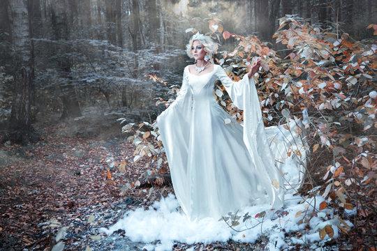 Fairytale Snow Queen portrait bringing winter in autumn forest.