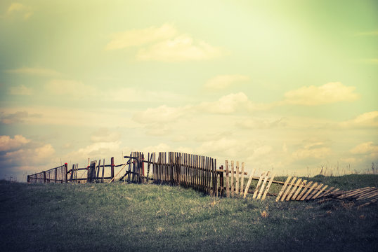 Sunny day in countryside. Summer landscape with old broken fence at pasture  under blue cloudy sky. Nature background in vintage style