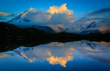 Fotomurales - Mountains and clouds reflected in Lac De Chéserys, Chamonix, France.