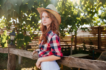 Cute smiling redhead cowgirl in hat leaning on ranch fence