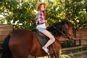 Cheerful woman cowgirl riding horse on ranch