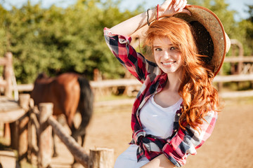 Happy woman cowgirl sitting and smiling on ranch