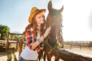 Smiling woman cowgirl taking care and hugging her horse
