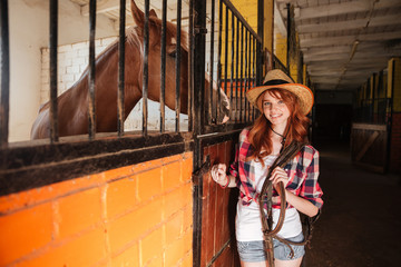 Cheerful woman cowgirl with horse standing in stable