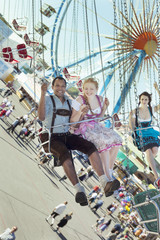 Couple having fun on chain carousel Ketten-Karussell at Oktoberfest