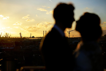 Silhouettes loving couple at sunset, cityscape.