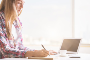 Woman using laptop and notepad