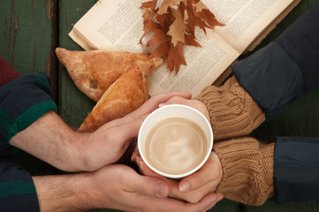 Loving couple holding hot coffee in hands on autumn background