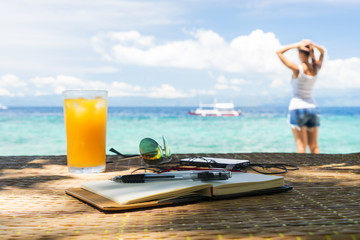 Relaxing girl, opened empty notepad is on the table with sunglasses, phone and headphones at the tropical sea background
