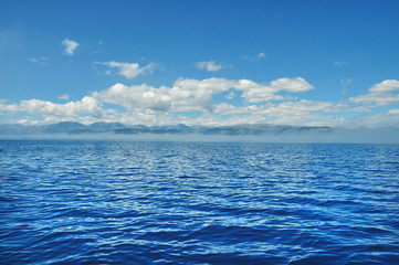 sea lanscape. blue sky, clouds over the surface of sea. mountain on horizon