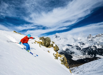 Skier skiing downhill in high mountains in fresh powder snow.