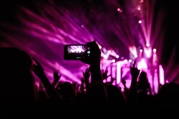 Hand with a smartphone records live music festival, Taking photo of concert stage, live concert, music festival, happy youth, luxury party, landscape exterior - purple light