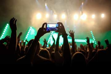 Rock concert crowd recording performance with digital smartphone, green guitar in stage