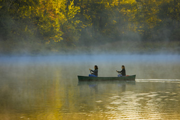 mother and daughter canoing in autumn