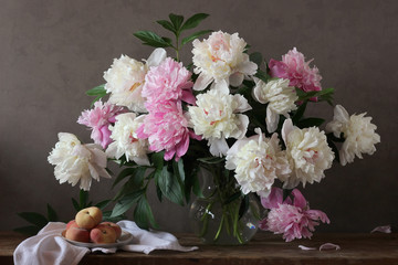 Still-life with a bouquet of peonies and peaches.