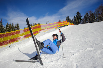 Young woman skier in blue ski suit after the fall on mountain slope. Sunny day. Ski resort. Winter sports concept. Carpathian Mountains, Bukovel