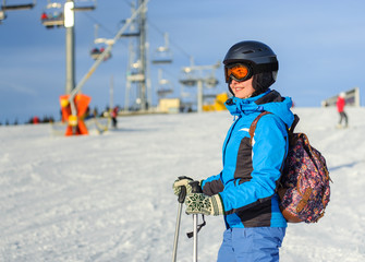 Close-up portrait of young happy woman skier at the ski resort on a sunny day against ski-lift. Girl is wearing blue jacket helmet and goggles. Ski resort at Carpathian Mountains, Bukovel, Ukraine