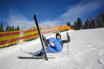 Young woman skier in blue ski suit after the fall on mountain slope. Ski resort. Winter sports concept. Bukovel