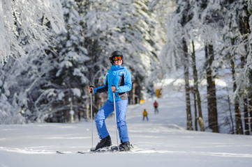 Portrait of young happy female skier is putting on her skis and looking to the sun on a sunny day against beautiful snow covered trees on the background. Ski resort. Bukovel, Ukraine