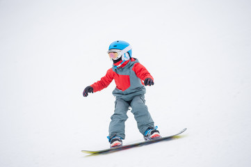 Snowboarder boy riding over the slope at the mountains overlooking the white snowy slope at a winter resort, extreme sport. Close-up