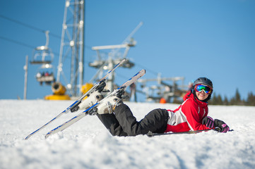 Woman smiling, lying with skis on snowy at mountain top in sunny day with ski lifts and blue sky in background.