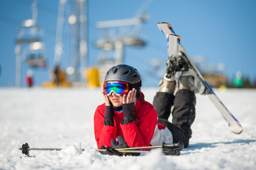 Smiling female skier wearing ski goggles lying with skis on snowy at mountain top and looking away in sunny day with ski lifts and blue sky in background. Close-up