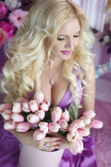 Beautiful blond woman with long wavy hair style in the purple dr