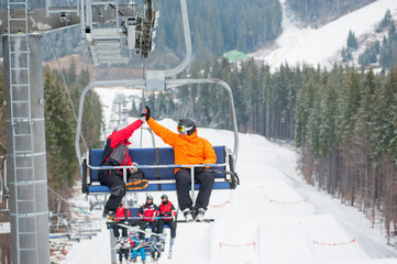 Two male ride the ski chair lift up the mountain together and giving each other a high five, having a fun time. Carpathian mountains, Ukraine