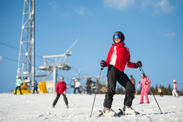 Woman wearing helmet, red jacket and ski goggles standing with skis on mountain top at a winter resort in sunny day with ski lifts and blue sky in background. Carpathian mountains