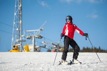 Woman wearing helmet, red jacket and ski goggles standing with skis on mountain top at a winter resort in sunny day with ski lifts and blue sky in background.