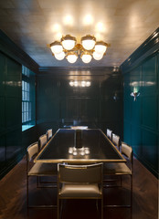 Glass dining table in high gloss teal wood panelled room