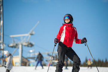 Portrait of female skier wearing helmet, red jacket and ski goggles standing with skis on mountain top at a winter resort in sunny day with ski lifts and blue sky in background.